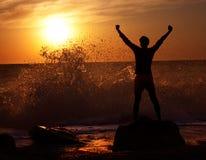 Homme à la mer orageuse sur le coucher du soleil Image stock
