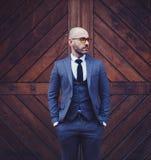 Homme à la mode contre le mur en bois photos stock