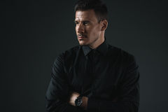 Homme à la mode dans l'équipement noir avec les bras croisés regardant loin, photos libres de droits