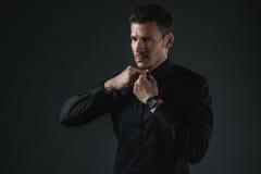 Homme à la mode dans l'équipement noir boutonnant sa chemise photographie stock libre de droits