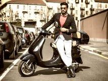 Homme à la mode en le scooter dans la ville Photographie stock