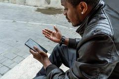 Homme à la peau foncée regardant l'écran de téléphone portable et s'asseyant sur des pas concrets photographie stock