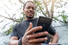 Homme à la peau foncée songeur dans le T-shirt noir regardant l'écran de téléphone portable image libre de droits