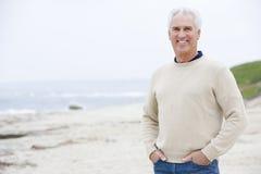 Homme à la plage avec des mains dans le sourire de poches Images stock