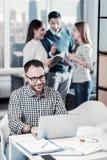 Homme à lunettes agréable s'asseyant et travaillant avec l'ordinateur portable Photo stock