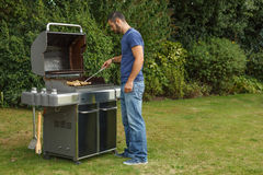 Homme à un gril de barbecue Images stock