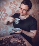 Homme à une tasse de café frais fort à un échantillon photos stock