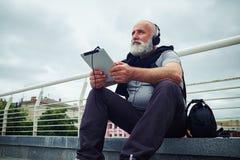 Homme âgé élégant dans des écouteurs avec la tablette se reposant sur a Photo libre de droits