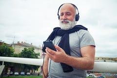 Homme âgé élégant dans des écouteurs avec le téléphone intelligent tenant l'ha proche Images libres de droits