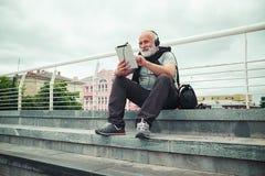Homme âgé élégant dans des écouteurs mettant en rouleau quelque chose dans COM de comprimé Photo libre de droits