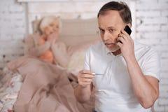 Homme âgé avec le thermomètre appelle l'urgence Image stock