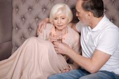 Homme âgé donnant le verre d'eau à l'épouse inquiétée Photos libres de droits