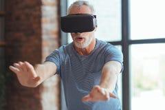 Homme âgé enthousiaste examinant des verres de VR Photo stock