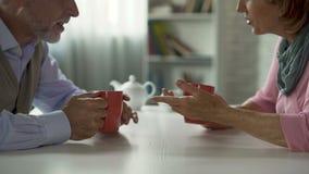 Homme âgé et femme parlant au-dessus de la tasse de thé à la table, amoureux d'école, se réunissant banque de vidéos