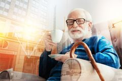 Homme âgé gai souriant tout en tenant une tasse de café Image stock