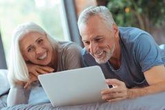 Homme âgé joyeux se situant dans le lit avec son épouse Photos libres de droits