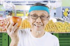 Homme âgé montrant une pomme saine Image stock