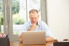 Homme âgé moyen à l'aide de l'ordinateur portatif à la maison Image stock
