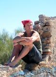 Homme âgé moyen bel s'asseyant sur un mur Images stock