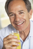 Homme âgé moyen buvant du jus d'orange frais Image stock