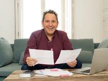 Homme âgé moyen réussi avec des fiches de paye, des factures et des finances de comptabilité informatique heureuses exempt des de images libres de droits