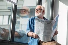 Homme âgé par aîné songeur s'asseyant sur le rebord de fenêtre Photographie stock