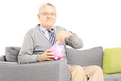 Homme âgé par milieu assis sur le sofa mettant l'argent dans la tirelire Image stock