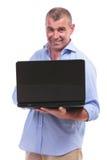 Homme âgé par milieu occasionnel tenant son ordinateur portable Photos stock