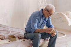Homme âgé sérieux ouvrant une vieille lettre Photo libre de droits