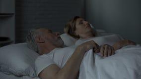 Homme âgé se situant dans le lit éveillé, regardant la femme dormant près de lui, mécontentement banque de vidéos