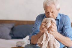 Homme âgé sombre s'affligeant au sujet de son épouse Image libre de droits