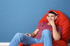 Homme écoutant l'audiobook par des écouteurs Photographie stock