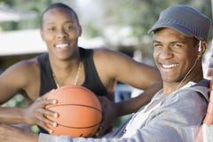 Homme écoutant la musique avec l'ami tenant le basket-ball Images stock
