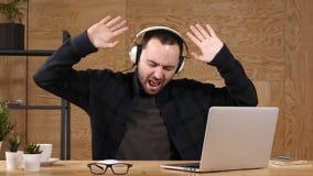 Homme écoutant la musique sur des écouteurs et chantant emotionaly, dansant clips vidéos