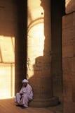 Homme égyptien s'asseyant par la colonne, temple de Philae Photo stock