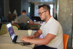 Homme élégant à l'aide de l'ordinateur portable dans le bureau Images stock