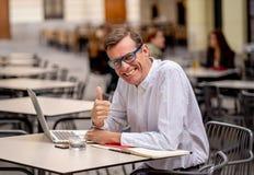 Homme élégant attirant heureux d'affaires mûres travaillant sur l'ordinateur portable montrant le pouce vers le haut du geste en  photos libres de droits