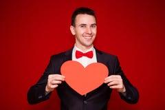 Homme élégant au coeur de livre blanc de prise de costume, avec le fond rouge Photos stock