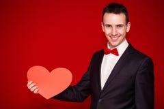 Homme élégant au coeur de livre blanc de prise de costume sur le backgroundt rouge Photographie stock
