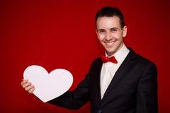 Homme élégant au coeur de livre blanc de prise de costume sur le backgroundt rouge Images stock