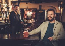 Homme élégant ayant l'amusement observant une partie de football à la TV et buvant de la bière pression au compteur de barre dans Images stock