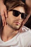 Homme élégant bel émouvant de jeune femme sensuelle dans des lunettes de soleil Photo libre de droits