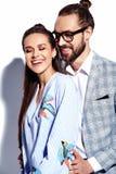 Homme élégant bel en verres dans le costume avec la belle femme sexy dans la robe colorée Image stock