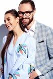 Homme élégant bel en verres dans le costume avec la belle femme sexy dans la robe colorée Images stock