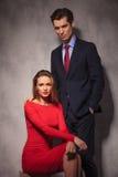 Homme élégant d'affaires se tenant derrière la femme assise dans la robe rouge Image libre de droits
