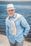 Homme élégant d'une chevelure gris avec des mains dans des poches à la rive Photos libres de droits