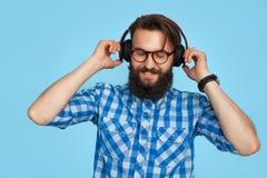Homme élégant dans des écouteurs sur le fond bleu Images libres de droits