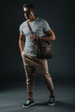 Homme élégant dans des lunettes de soleil tenant le sac en cuir brun et posant dans le studio photos libres de droits