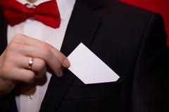 Homme élégant dans la carte de visite professionnelle de visite blanche de prise de costume sur le fond rouge, foyer sur la carte Photo stock