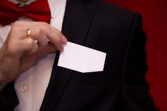 Homme élégant dans la carte de visite professionnelle de visite blanche de prise de costume sur le fond rouge, foyer sur la carte Photographie stock